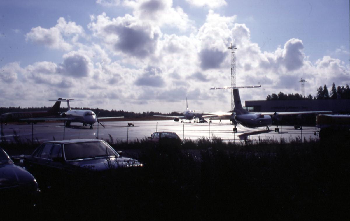 Lufthavn, 4 fly på rullebanen.  3 kjøretøyer i forgrunnen.