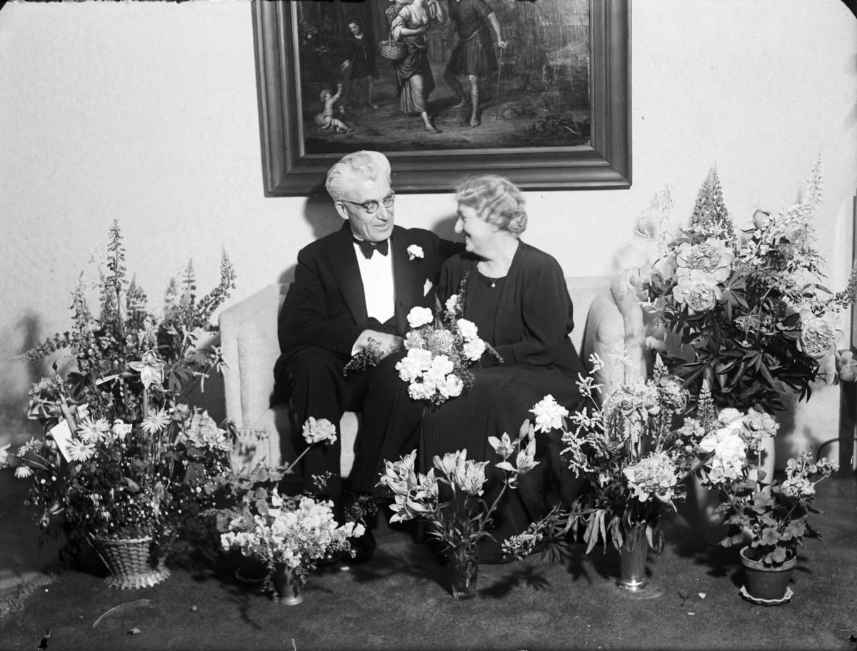 Moster Anna Olsson med man omgivna av blommor.