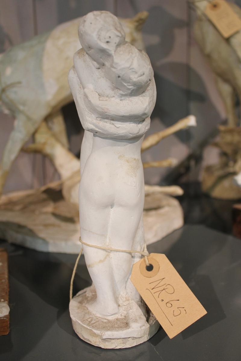 """Skulptur i gips av to mennesker som holder rundt hverandre. Tittel: """"OMFAVNELSE"""" fra 1936"""