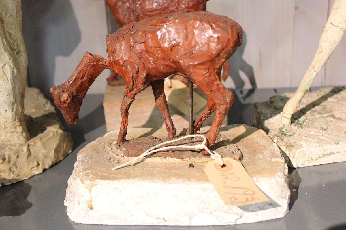Skulptur av hjortedyr i rødbrunt kitt på sokkel av gips. Denne var et utkast.