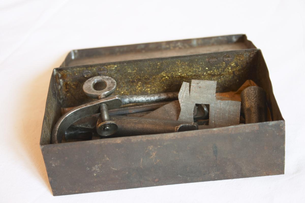 Diverse pregeverktøy og utstyr til skomakermaskine. Disse ligger i en metall-eske.