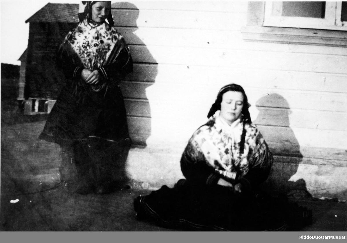 Nieiddat viesu olggobealde. Jenter utenfor et hus.
