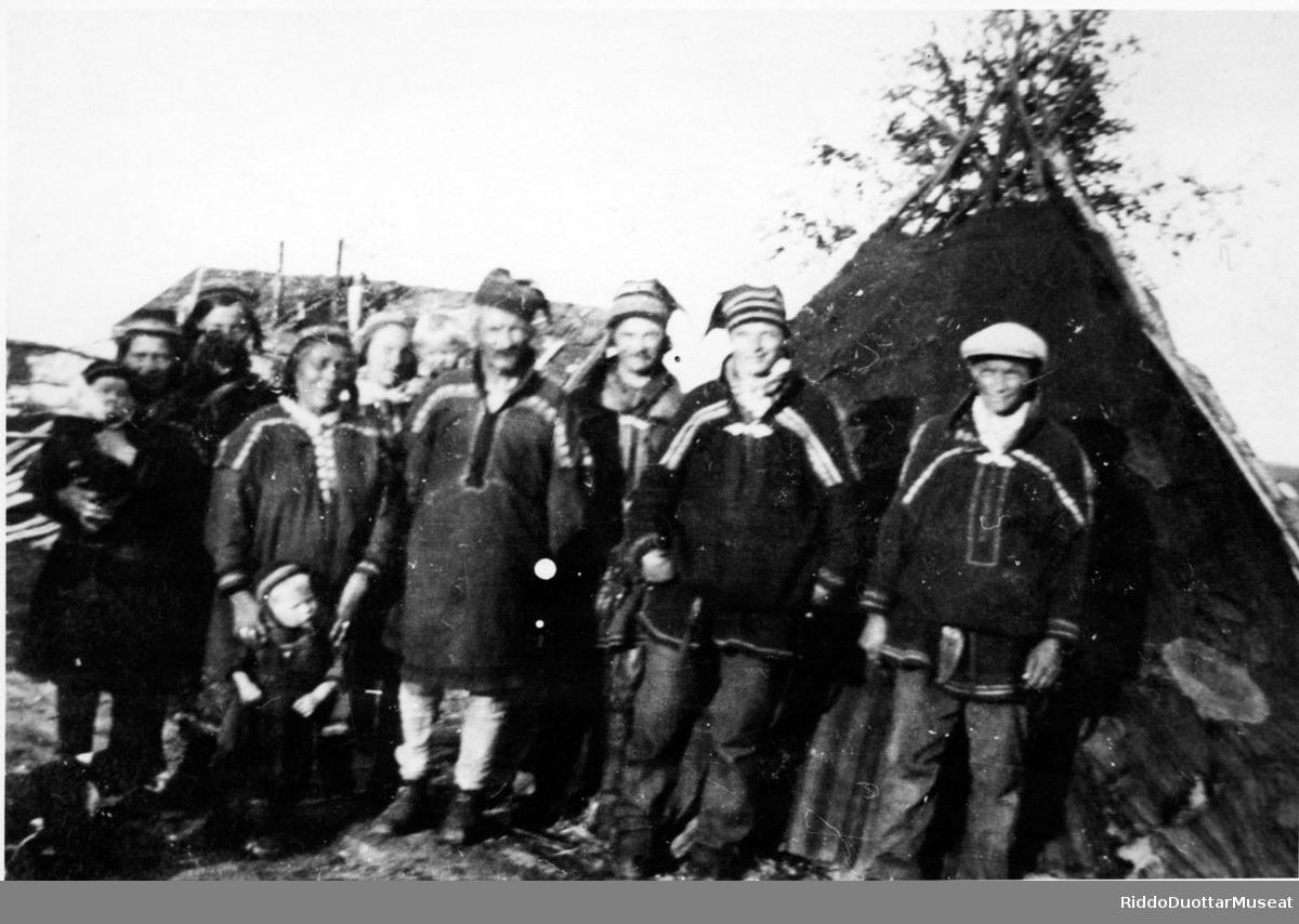 Olbmot coahkkanan govvemii lávvogurrii. Folk samlet til fotografering med lavvo i bakgrunnen.