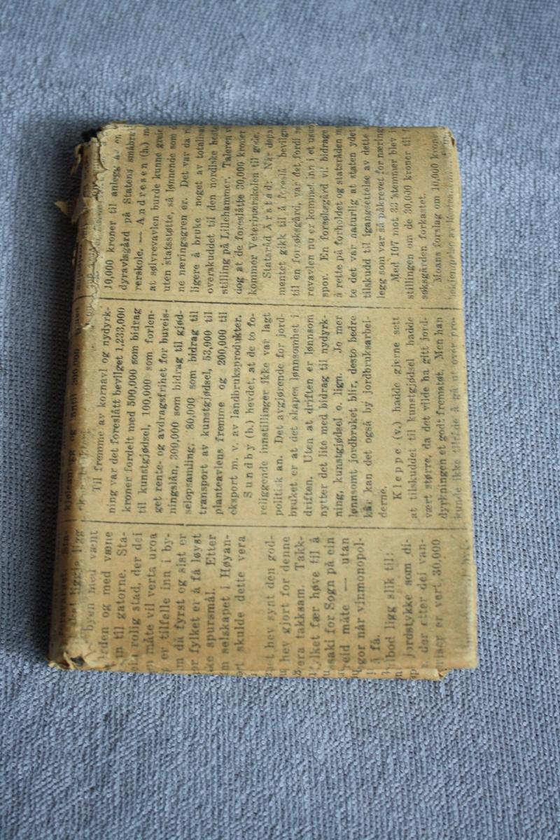 Bok pakka inn i avispapir. Avia er frå ei utgåve av Bergens Tidene frå ons. 4. juni 1930.