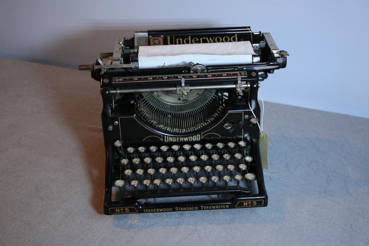 Underwood no5 skrivemaskin. Manglar bokstaven Å.  Firmanamn med logo på topp av maskin.