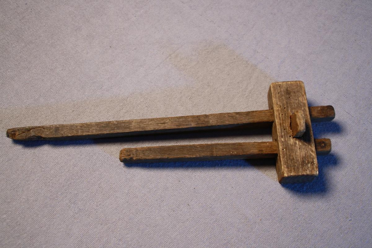 Strekmål, med to firkanta pinnar av ulik lengde. Den lengste pinnen er noko øydelagt. Låg i kiste KSF.000227.