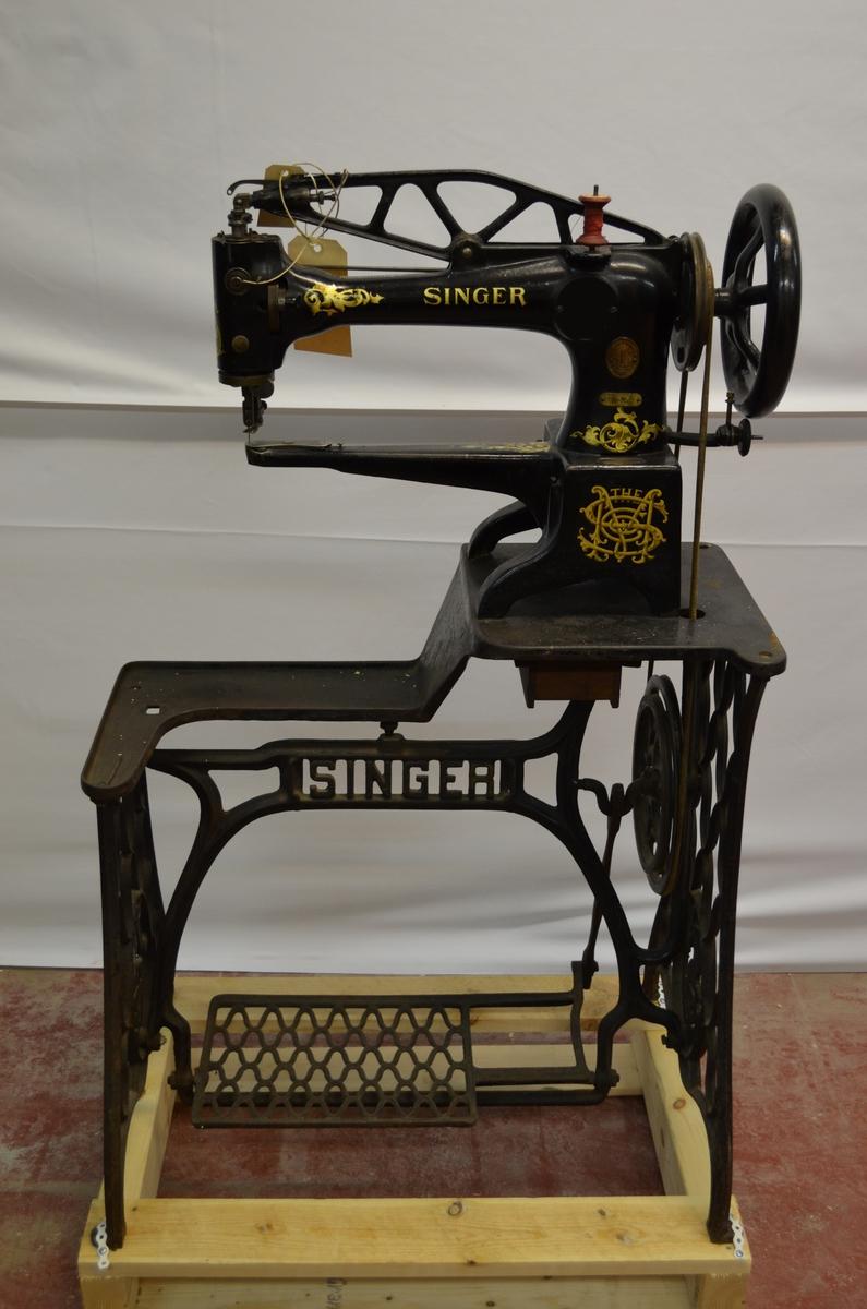 Symaskin fastmontert på bord.Symaskina er modell Singer med dekorasjon i gull (gylne blad). Utforminga av bordet tilseier at dette er ei symaskin som vart nytta av segl- eller skomakarar,