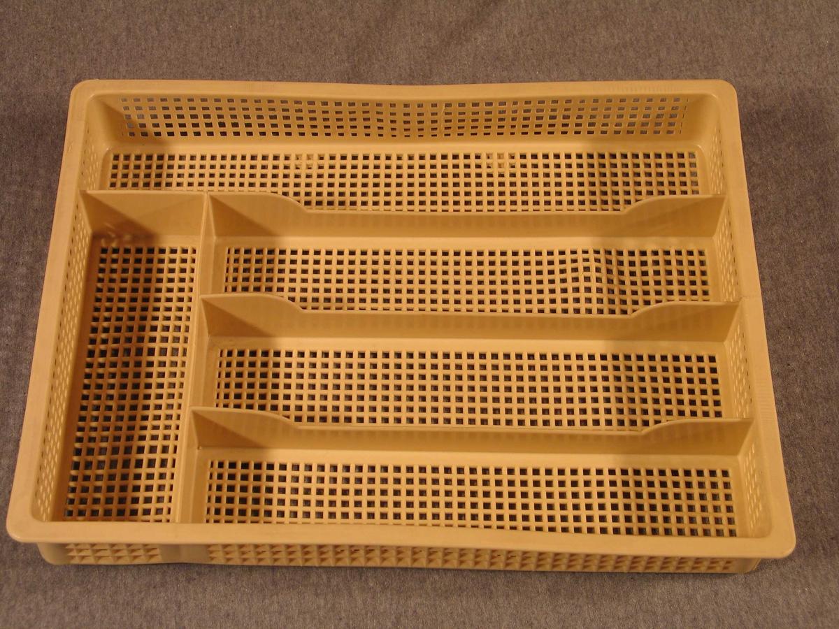 Rektangulær kasse som skal setjast i kjøkkenskuff. Inndelt i 5 felt; tre like store for knivar, gaflar og skeier, eit lite for teskeiaer og det lengste for knivar og annan lang kjøkkenreiskap. All overfalte unnateke skilja mellom felta er støypt som neting med kvadratiske ruter.