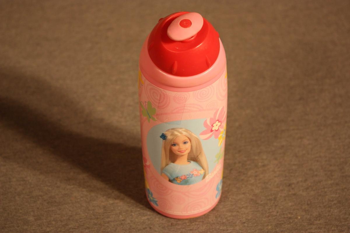 Plastflaske  med skrukorkog drikketopp. Flaska er forma til handgrep. Pålimt etikett med brystbilete av ei Barbiedokke i midten. Skrive Synne E. med tusj under botnen.