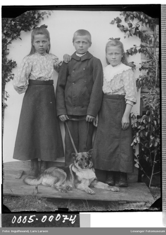 Gruppebilde av to jenter og en gutt med hund i bånd.