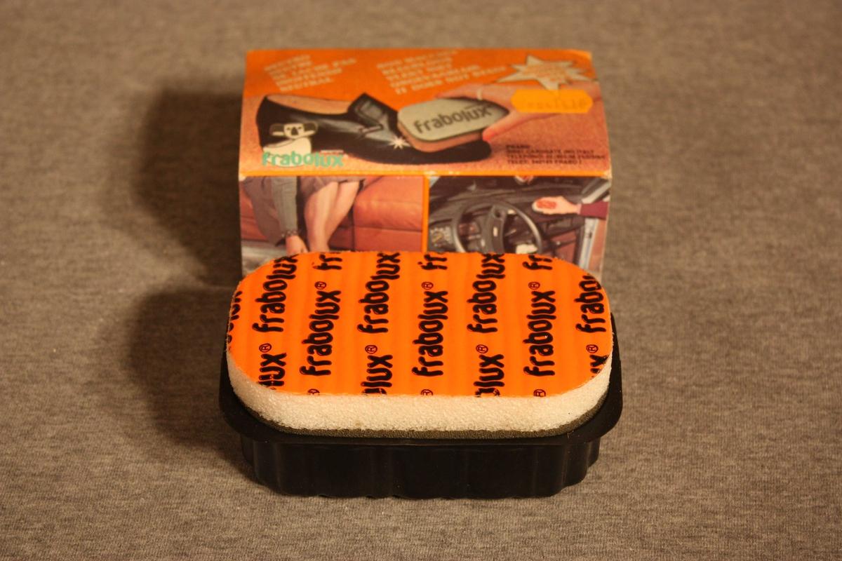 Svamp innsett med feitt er festa til ein haldar - eller boks - i plast. Utanpå er eit papphylster med bilete av svampen brukt p ein svart sko. På hylsteret er beskrivelse av bruksområde på italiensk, spansk,. fransk, engelsk, tysk,og nederlandsk. Middelet kan brukast til å rense og pusse sko, vesker, belte, hanskar, syntetisk skinn, møblar og innvendes i bilar. Orange prislapp: 14,10