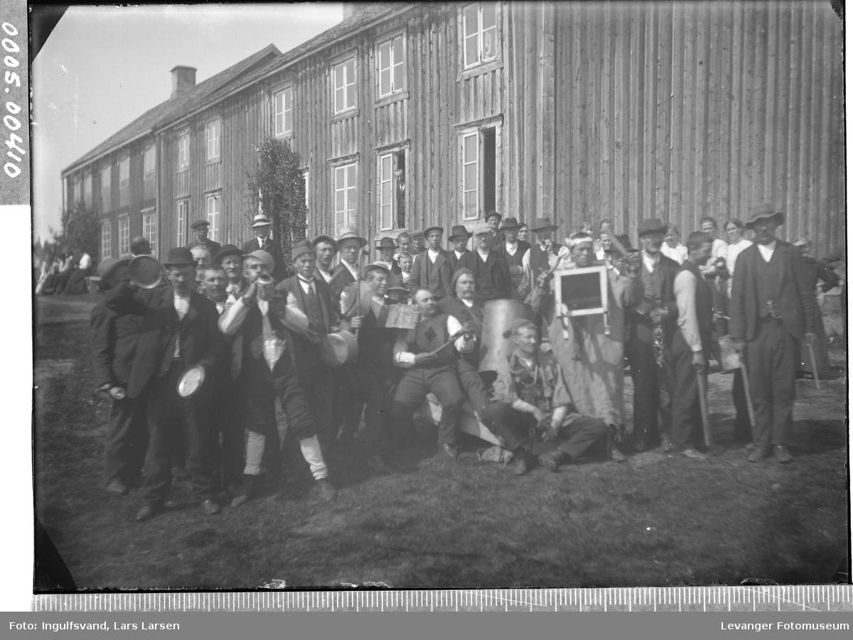 Gruppebilde av en mengde mennesker  foran et våningshus, bryllup andre dagen.