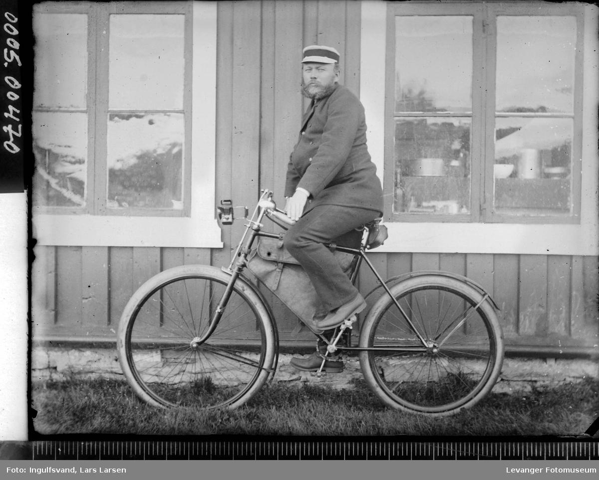 Portrett av en mann på sykkel foran en fasade.