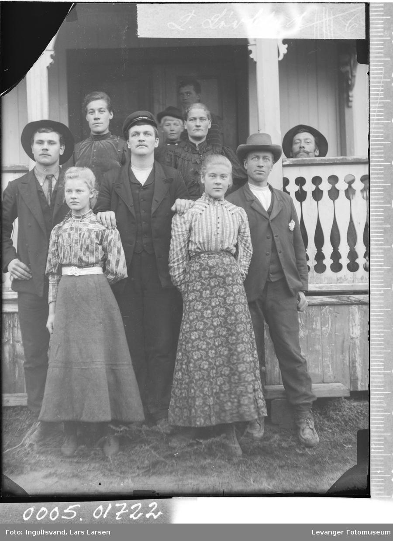 Gruppebilde av fire menn og fem kvinner ved et inngangsparti.