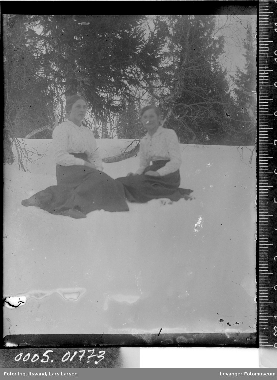 Portrett av to kvinner som sitter i snøen.