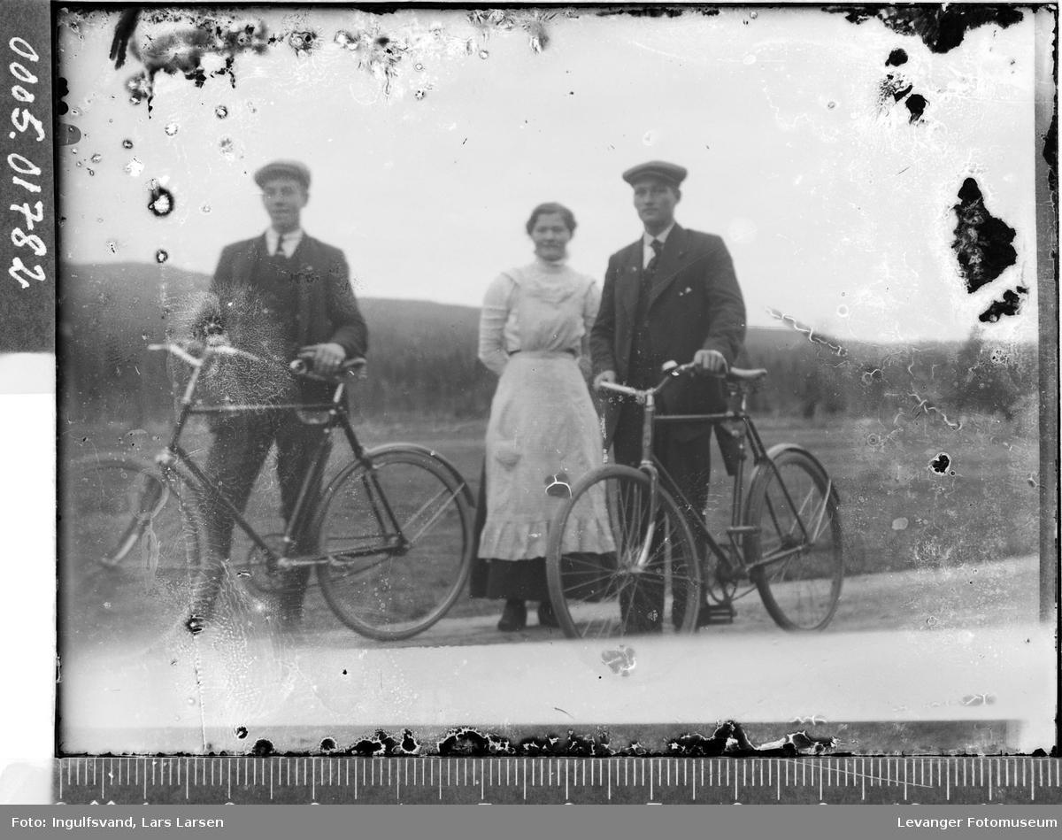 Portrett av to menn med sykler og en kvinne.