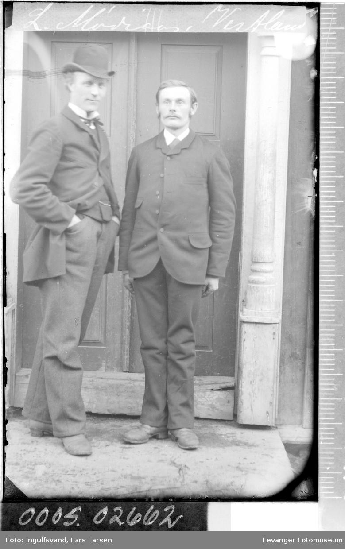 Portrett av to menn foran et inngangsparti.