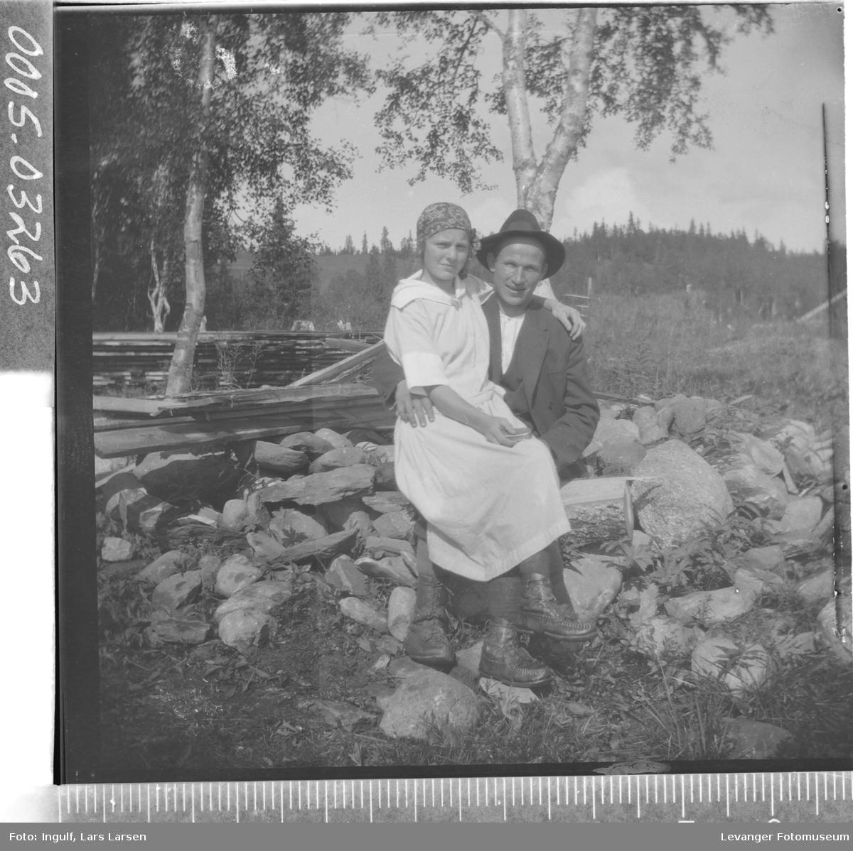 Portrett av kvinne og mann som sitter i en steinrøys.