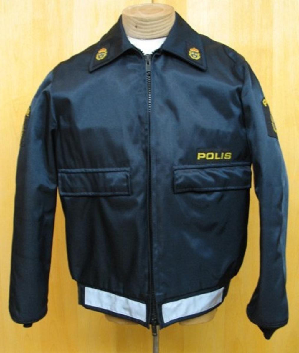 Uniformsjacka för polisman. Jackan är mörkblå och tillverkad av vernyl (yttertyg), trilubal, polyamid och polynosic (innertyg) acryl (foder). På ryggen finns texten ''POLIS'' i 8 cm. höga bokstäver av reflextyg.  Längs midjan finns ytterligare tre band av reflextyg. På båda överärmarna finns polisens vapen och texten ''POLIS'' påsytt. Polisens vapen finns även på kragens spetsar. På vänster bröstsida finns en tygetikett med texten ''POLIS'' i gult på svart botten. Jackan stängs med dragkedja.