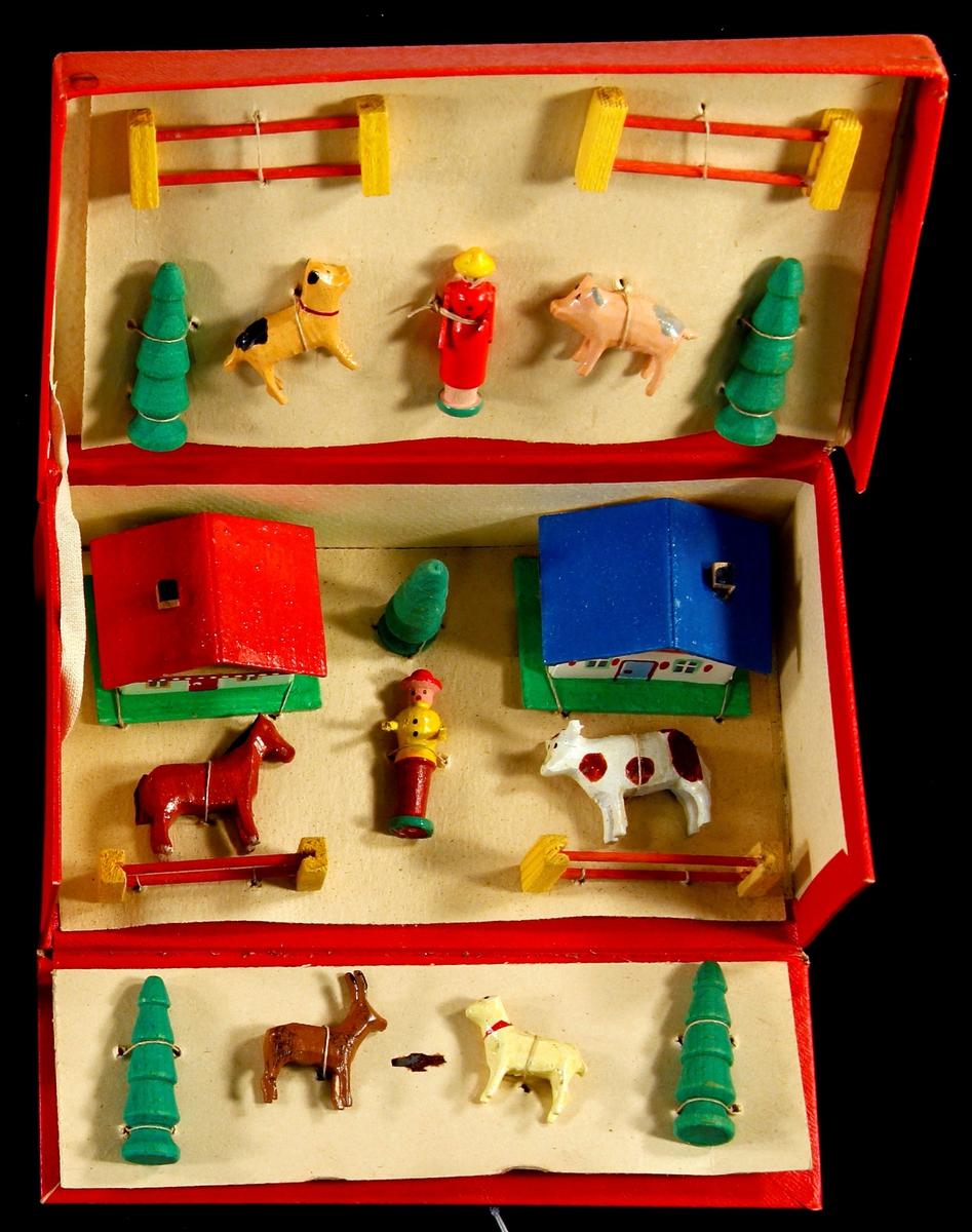 Små dyr, hus, dyr ,gjerder og trær  i miniatyr. Malt i friske farger. Ligger fastmontert i rød pappeske som kan brettes ut ved åpning. To hus, 6 dyr, 2 personer, 5 trær, 4 gjerder.