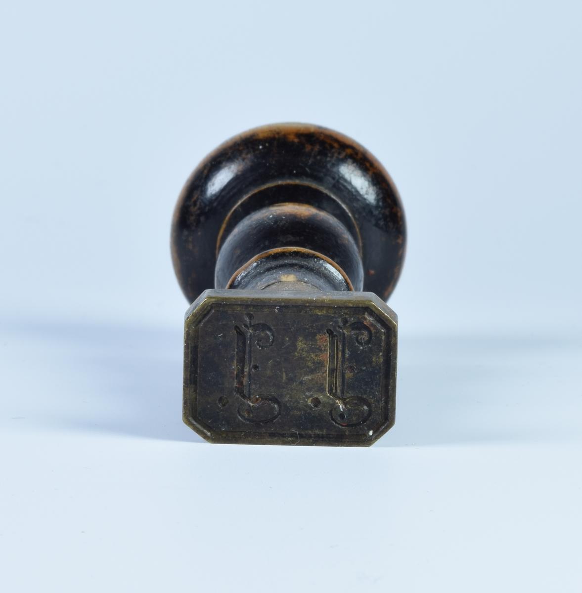 Signetstempel med grep av tre og stempel av metall. Signetstempelet har innitialene J. J,