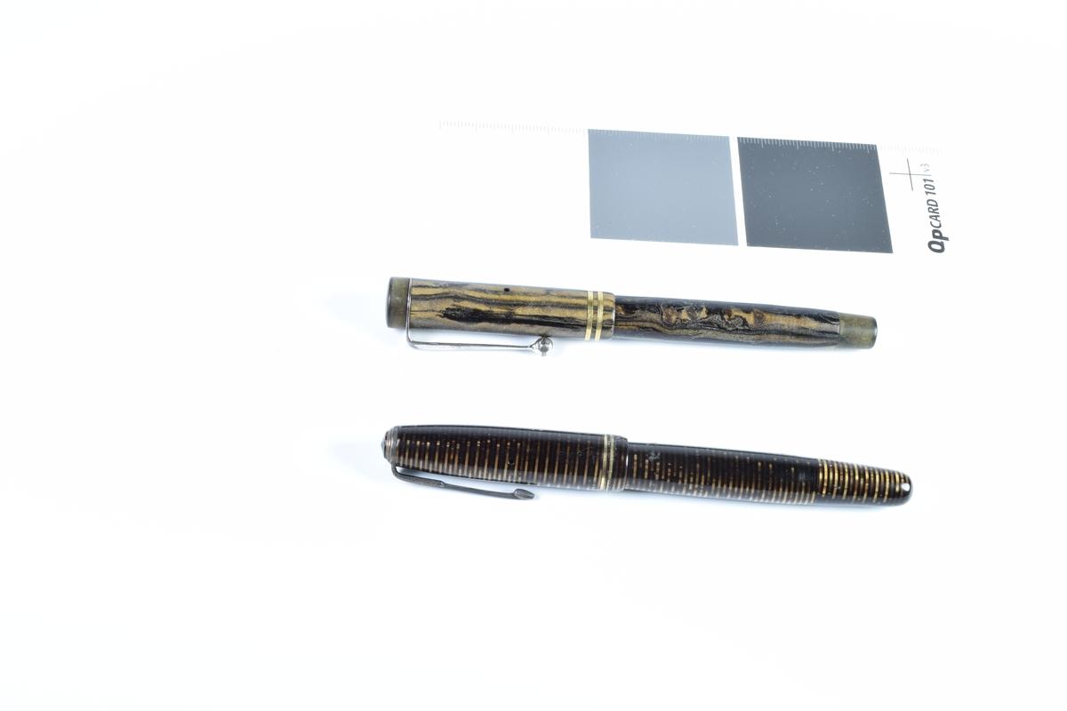 To fyllpenner med splitt. Penn a er dekorert med et et langsgående mønster i sort og brunt, og penn b er dekorert med mørke og sorte striper rund kortsiden av hele pennen. Begge pennene har i tillegg to forgylte striper nederst på hetten.