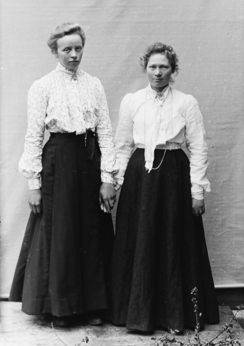 To stående kvinner i helfigur, holder hverandre i hendene, foran lerret. Gjertrud Lo (f. Høverstad) til venstre, kvinnen til høyre ikke navngitt