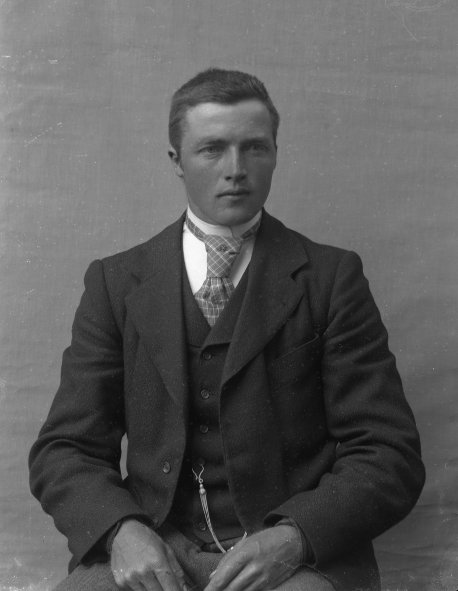Dresskledd mann foran lerret