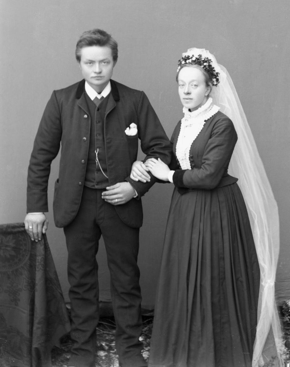 Ungt brudepar. Bruden i mørk kjole, blomster i håret og hvitt slør. Fotografert utendørs med lerretbakgrunn