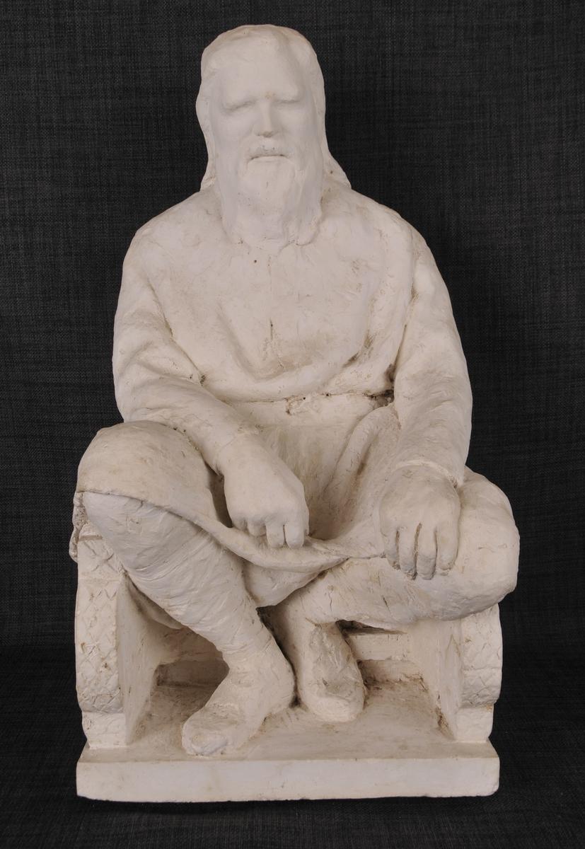 Ein mann med langt hår og skjegg sit i ein høgrygga stol som er rikt utskoren på sidene og i ryggen. Mannen har på seg lang kjortel med belte i livet.