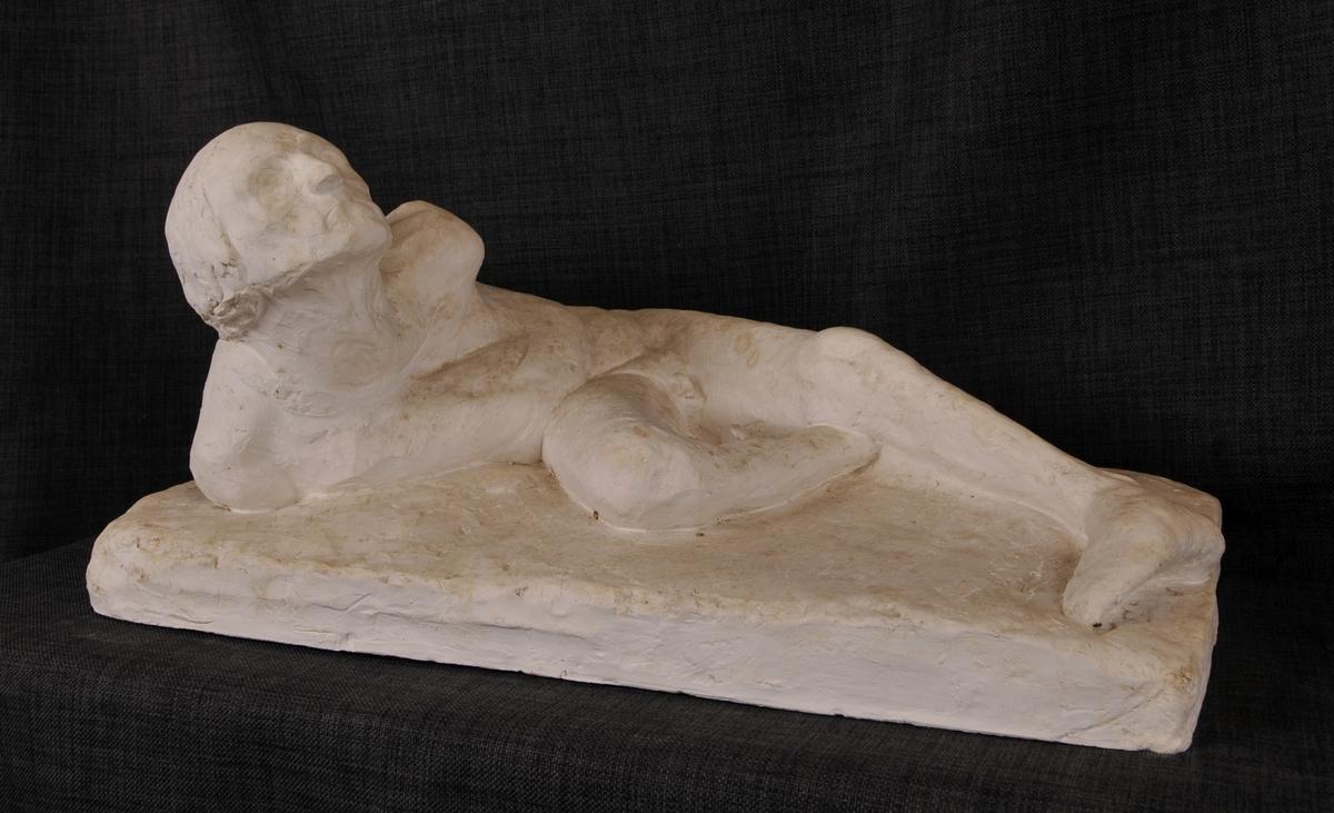 Eldre mann, liggande figur, dels deformert.