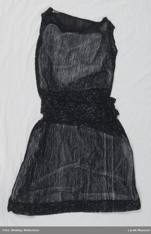 Form: a)kjole:sort bobinett,jevnt oversydd m sorte glassperler,11 cm br. belte oversydd m mønster- virkning av avlange perler som kjolen,effekter av pletter m glatt og fasettert overflate,trykknapplukking,gas-overdel, rett avslutning av perlebrod. under armen,ovenfor sort flor som danner smale skulderstropper og båtutr.overdel 44 cm perle brodert.52 cm skjørt b)underkjole:sort silke,sårk. ø. splitt n c)underkjole d)en 18 cm br. bord av sort bobinett brod.m perle 98 c) L:60 + seler
