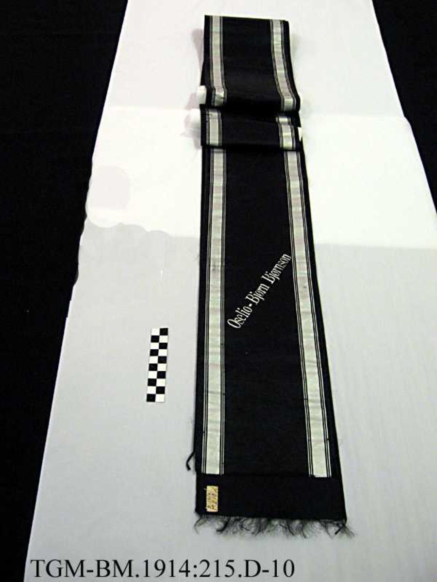 Båndet er sort med sølvstriper og sølvskrift.