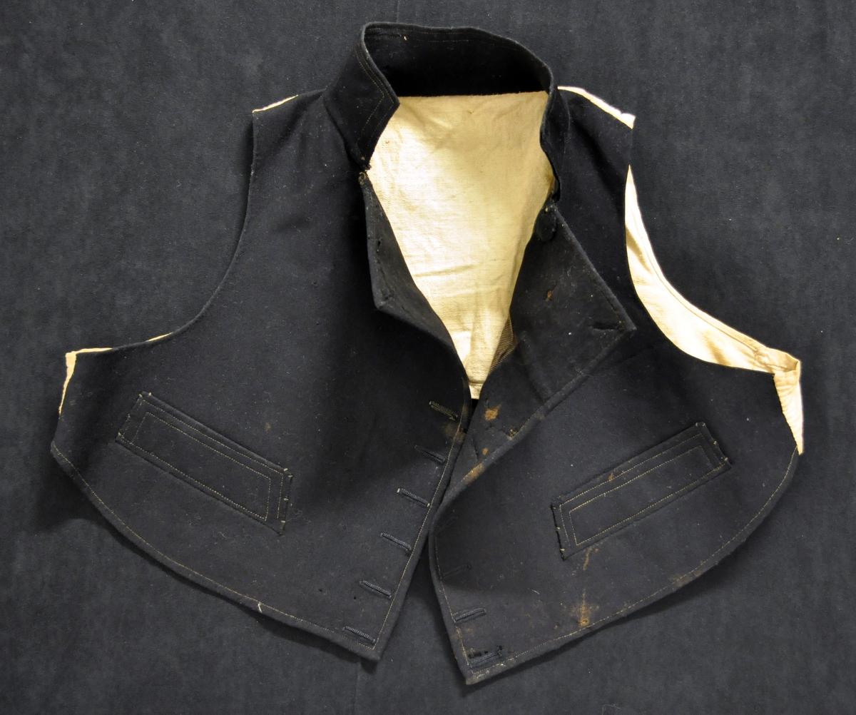 """Øst-Telemarks mannsdrakt med rød trøye, sort vest og lange, grå bukser med påsydd """"akantus""""-bord i sidene og framme i livet. Fra protokollen: Lars Fykeruds konsertbunad. En mengde tinnknapper i jakken, vesten og i buksebenas sider. Buksen har grønt tilklippet akantus-motiv i sidene. A) Rød vadmelstrøye med svart kanting B) Svart klede-vest C) Grå vadmelsbukse, lang  Vesten mangler knappene, det er 14 knapphull."""