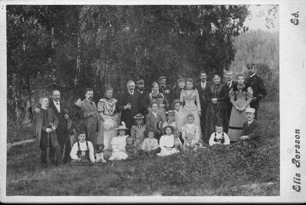 Dals-Ed, En samling finklädda människor, barn och vuxna, står och sitter i gräset.