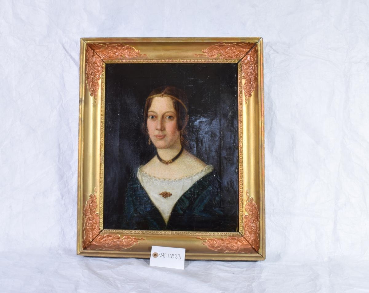Halvportrett av en kvinne. Festkledd med vid utringning. Lange øredobber og brosje. Halsbånd laget i hårarbeid.