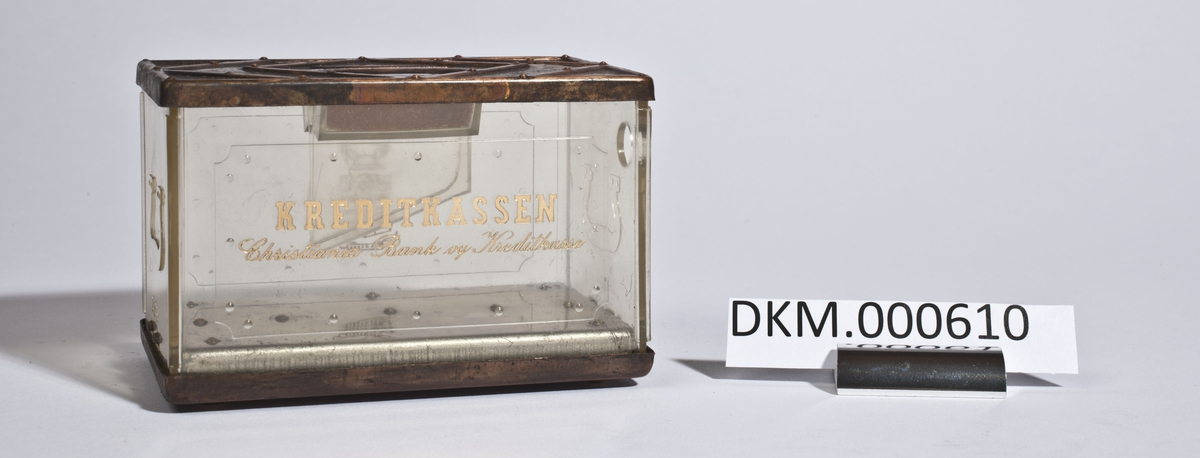 Sparebøsse i form av en rektangulær kasse med lokk. Den har vegger av gjennomsiktig plast.