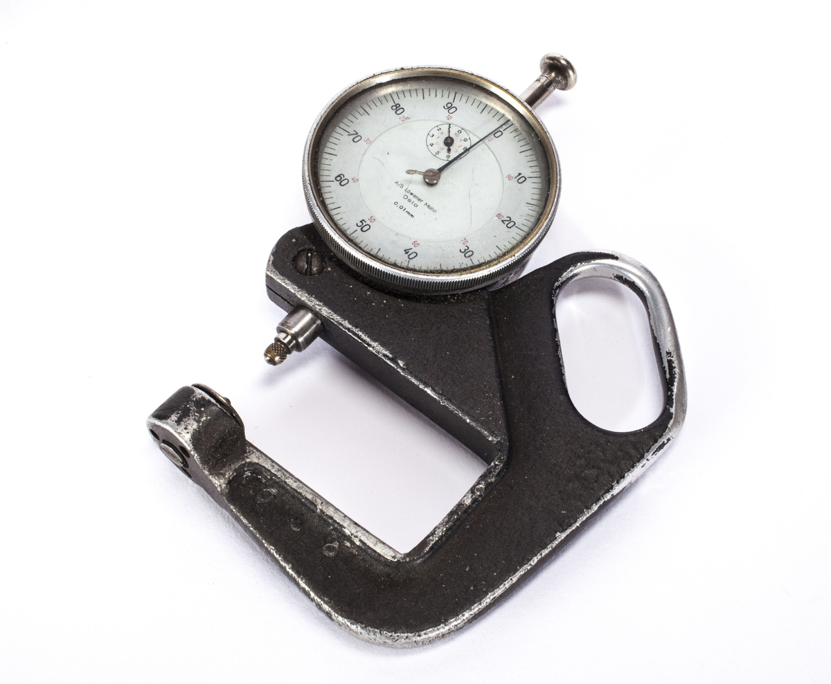 Måleklokken har en rund skive med måleskala fra 0 til 100 og visere. Festet på en holder med håndtak.