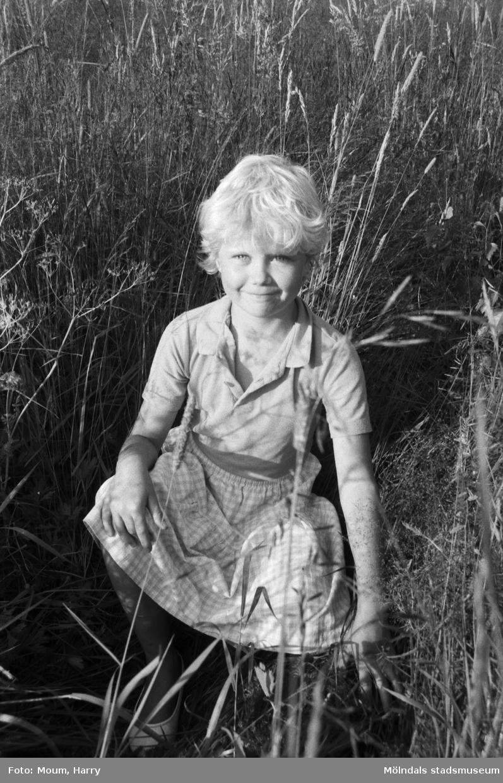 """Eva i gröngräset, år 1984. Fotografi taget av Harry Moum, HUM, och publicerat i Mölndals-Posten, vecka 31, med bildtexten: """"En liten Eva på sommarängen som njuter av barfota springa kring i gräset."""""""