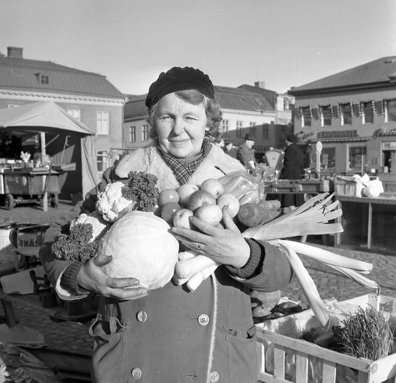 """Enligt notering: """"Grönsaker på torget en tant har famnen full 8/2 1961""""."""