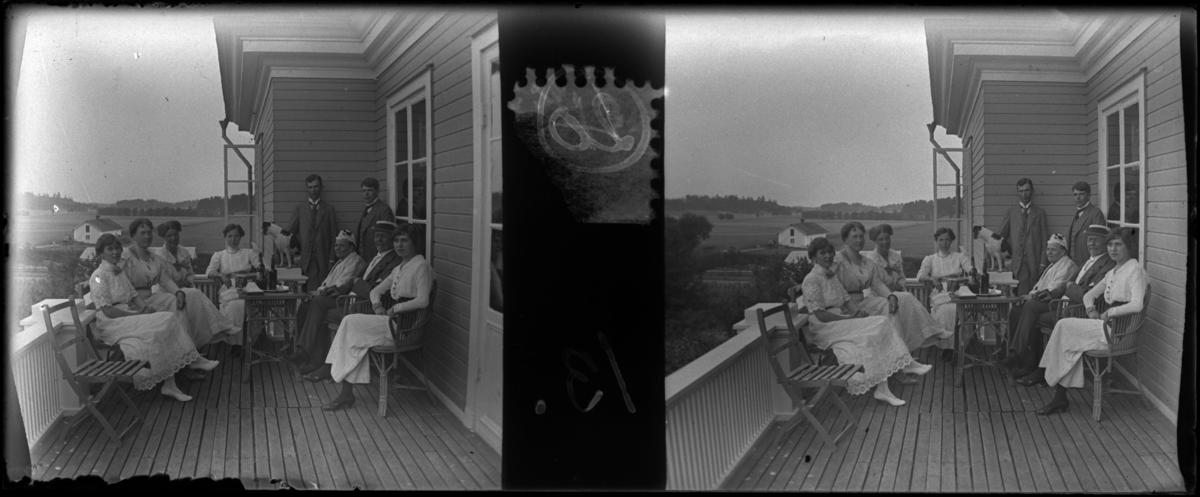 'Bildtext: ''Lofthus: Åda, group on balcony.'' :: Gruppbild med 6 kvinnor varav 1 äldre och 2 män samlade på veranda / balkong. Sittande vid möblemang med litet bord i ev. rotting, på bordet glasflaskor med kork. 1 hund med på verandan. Trästol. Hus. Kläder. ::  :: Ingår i serie med fotonr. 5249:1-20, se även hela serien med fotonr. 5237-5267.'