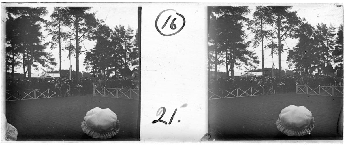 'Bildtext: ''Skyttefesten.'' :: I förgrunden hattklädda huvuden och tom yta i form av trägolv med trästaket runt ev. dansbana. På andra sidan ev. ett bord och en cykel samt folksamling, män, kvinnor, barn och skylt ''Tombola''. Flaggstång. Lykta. Kläder ev. några i uniform. ::  :: Ingår i serie med fotonr. 5257:1-18, se även hela serien med fotonr. 5237-5267.'
