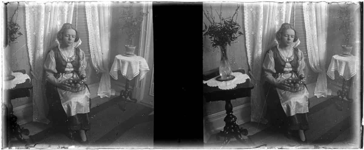 'Bildtext: ''Rhoda, utklädd.'' :: 1 flicka, Rhoda, sittande på stol i ett rum, iklädd klänning, smycke, halsband,  hållande glasskål med äpplen i knäet. I rummet spetsgardiner, matta, bord, stol, blomvas. Kläder. Möbler. ::  :: Ingår i serie med foronr. 5265:1-12. Se även hela serien med fotonr. 5237-5267.'