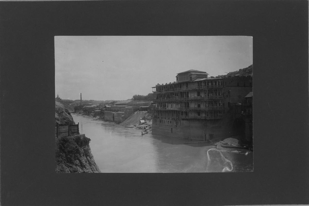 'Vy med flod med stora hus byggda ner invid vattent, balkonger mot floden. I vattnet ekor med människor. ::  :: Ingår i serie med fotonr. 5288:1-30. Se även fotonr. 5269-5292 med bilder från Stuxbergs resa till Kaukasien.'