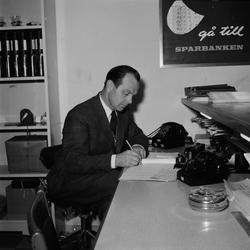 Tage Carlsson sitter och skriver, sannolikt Sparbanken,, Upp