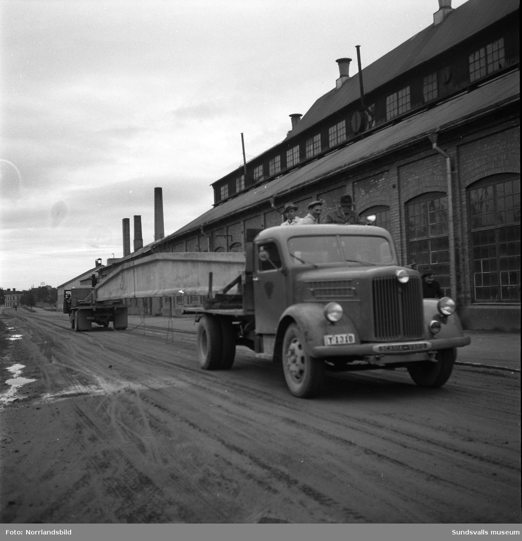 Bil & Buss fraktar gigantiska takstolar till sitt nybygge på Fabriksgatan. Det krävs dubbla lastbilar och chauffören i den bakre lastbilen får backa hela vägen.