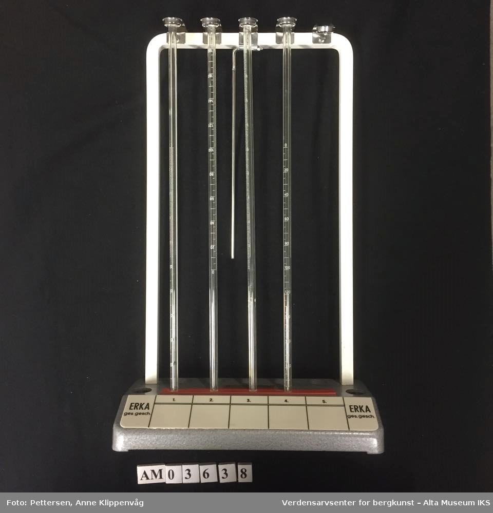 Stativ i metall med fire tynne glassrør. Avlang, kvadratisk fot med plass til fem prøverør. Prøverørene holdes fast med en metallklemme på toppen av stativet.