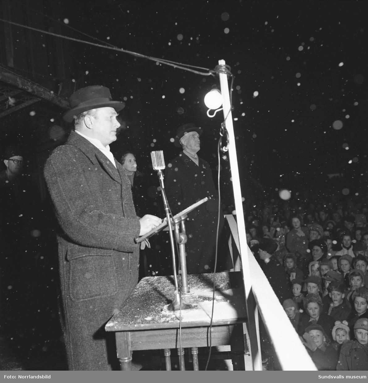 Högtidlig invigningsceremoni av Svenska skidspelens på Stora torget i Sundsvall. Snön faller och torget är fullpackat av folk.