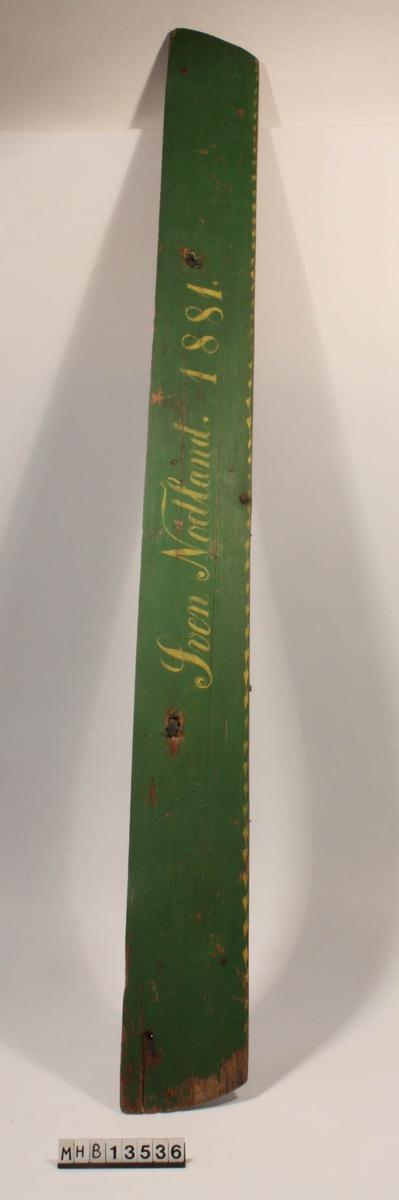 Fjøl fra toppen av et skap. Den malte fjøla er festet til en umalt fjøl med trenagler og metallbeslag. Gul, malt bord i nedre kant.
