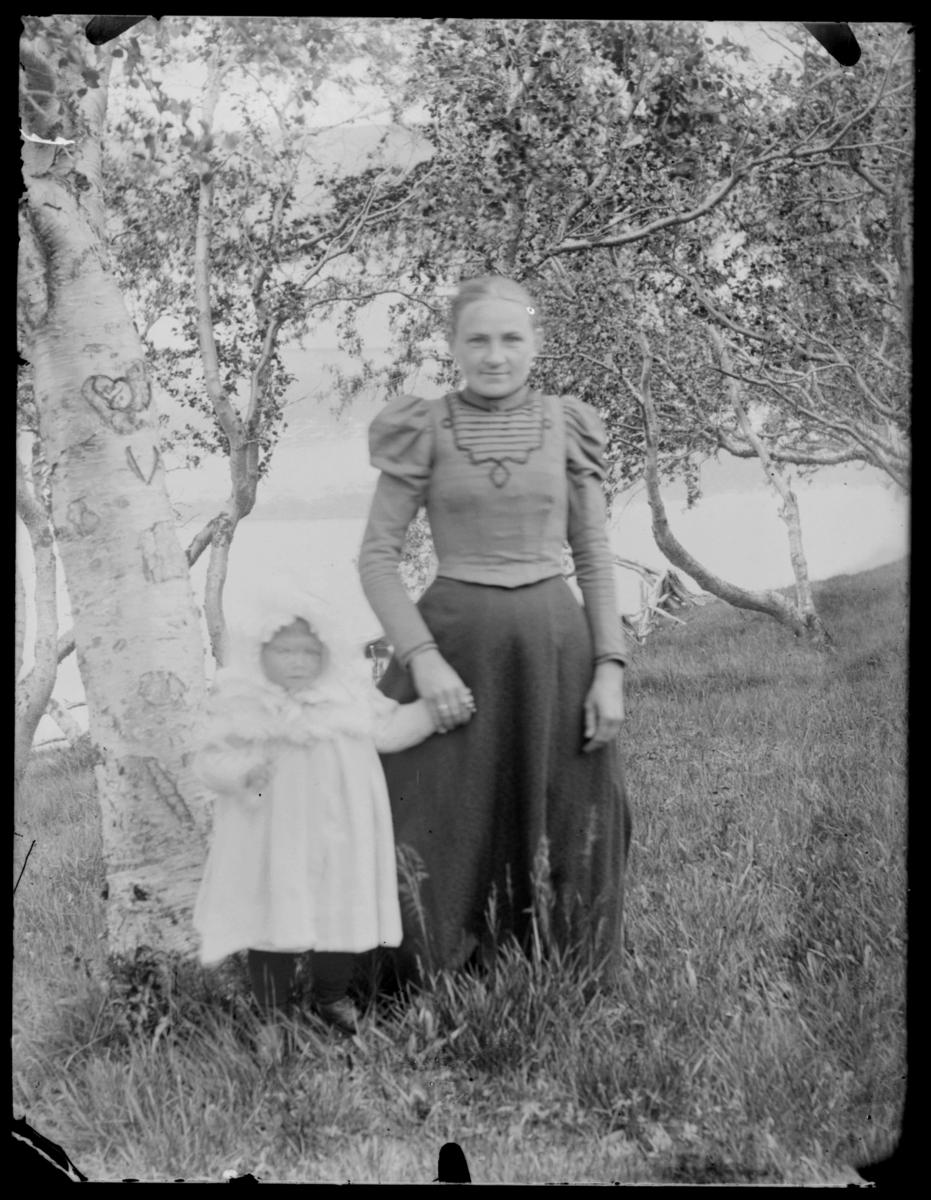 Vilhelmine Gunhild Methi med en liten jente stående ute ved bjørketre med hjerte i barken